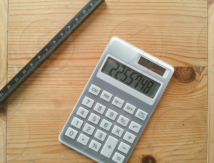gray and white standard calculator reading 2255748 near black measuring ruler on brown wooden surface photo