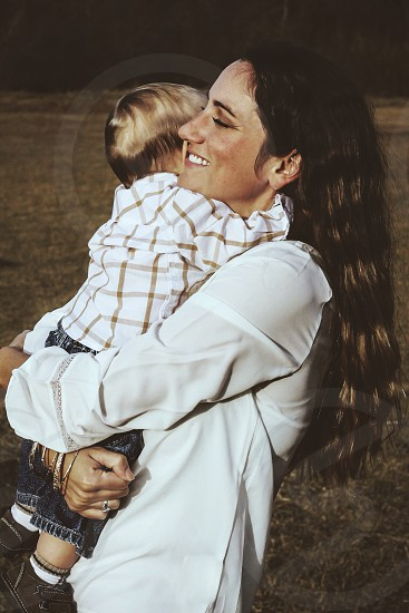 woman in white long sleeved shirt carrying a baby boy photo