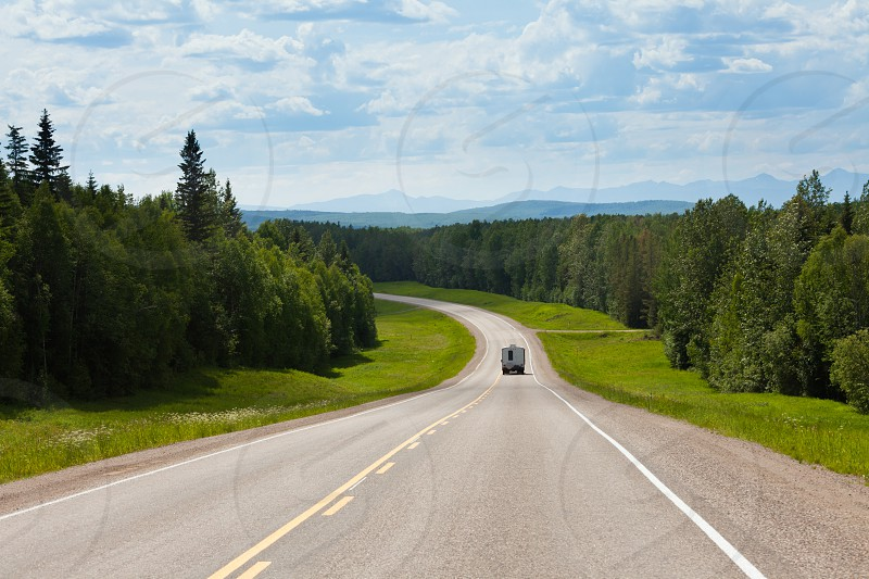 Recreational Vehicle RV on empty road of Alaska Highway Alcan in boreal forest taiga landscape south of Fort Nelson British Columbia Canada photo