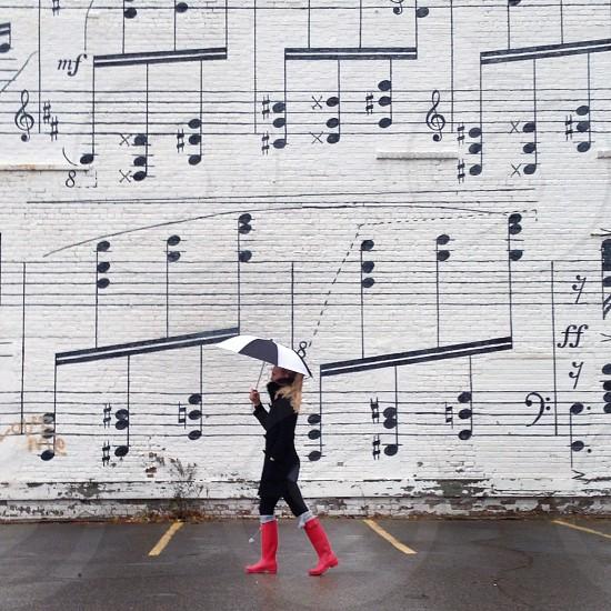 woman walking near white musical note printed wall  photo
