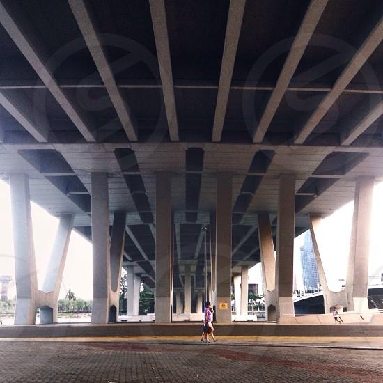 woman walking on road under bridge photo
