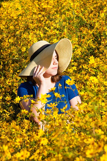 Girl in sun hat in a sea of sunflowers. photo