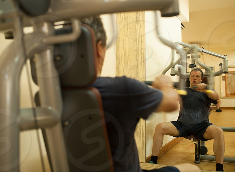 Mature man working out on shoulder press machine. Regular physical activity for keeping fit and healthy. Shot in motion and mirror reflection photo