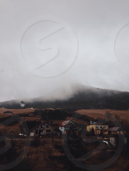 fog covered hill behind houses on slope photo