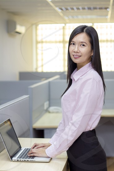 business woman working in the office wearing business attire working on a laptop photo