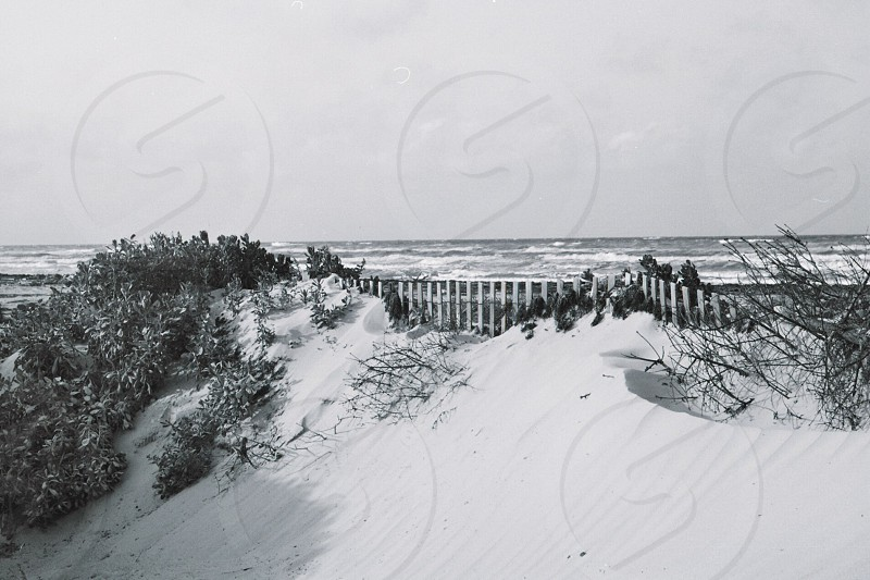 grayscale photo of bridge on hill with snow photo