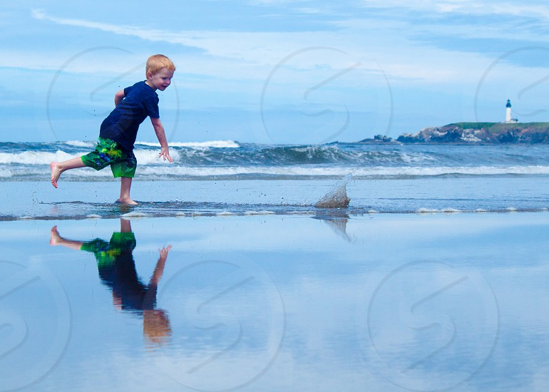 Boy on Beach at Ocean Throwing Rock into Water With Reflections photo