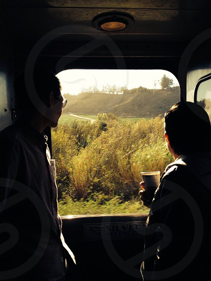2 men looking out car window photo