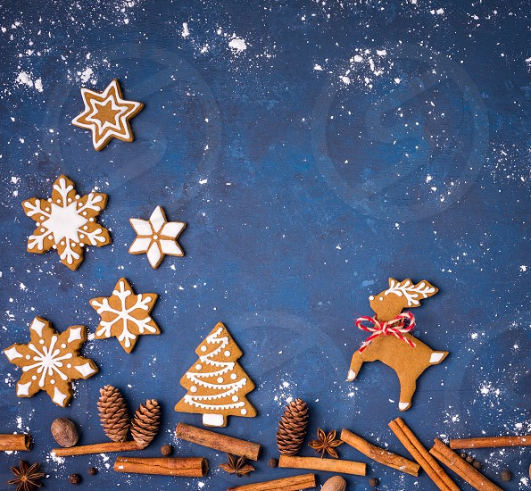 Gingerbread cookies with spices creating a snowy Christmas forest scene with reindeer and tree over a blue background. photo