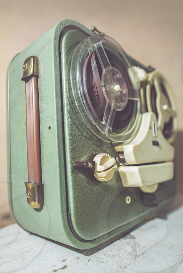 Old vintage green tape recorder on pink wall photo