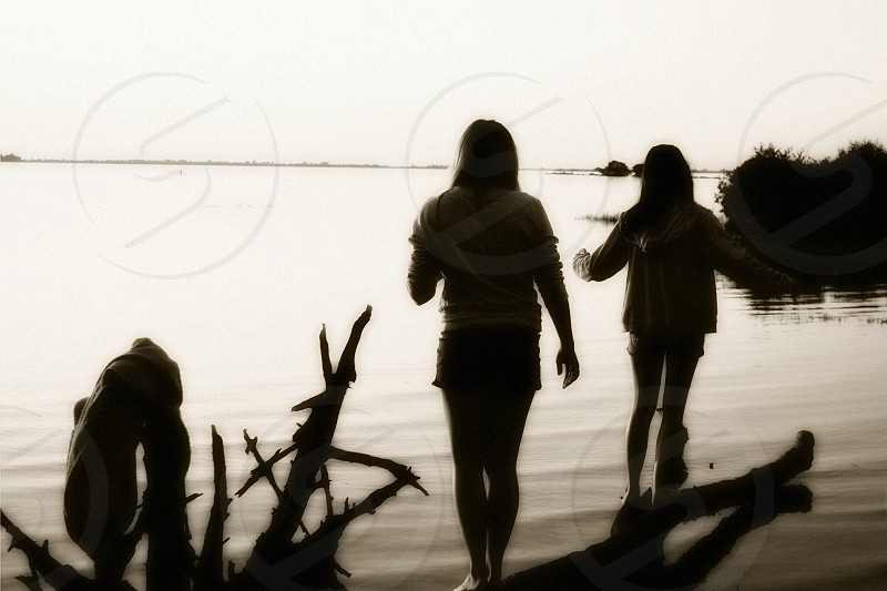 girls best friends playing driftwood water reflection island balance photo