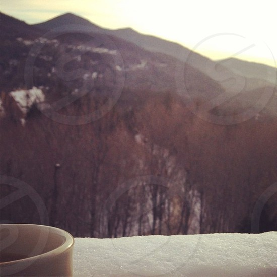 Drinking coffee over looking snow covered mountains. New Hampshire. photo