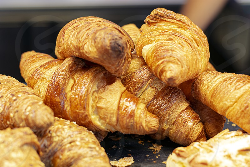 a group of croissants stacked on a tray. Baked product. photo