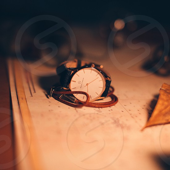 tilt shift photography of silver analog watch beside dried leaf photo