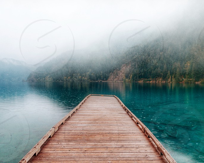 brown wooden dock surrounded with water near green trees covered mountains at daytime photo