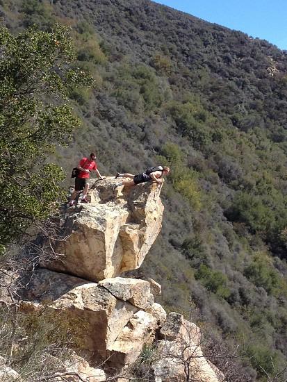 mans climbing large boulders photo