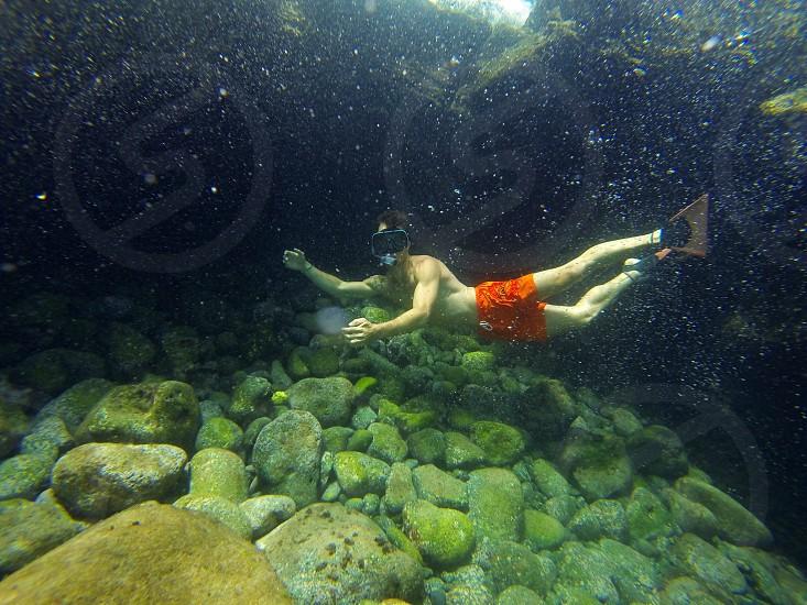 man in red swim trunks underwater near rocky bottom photo