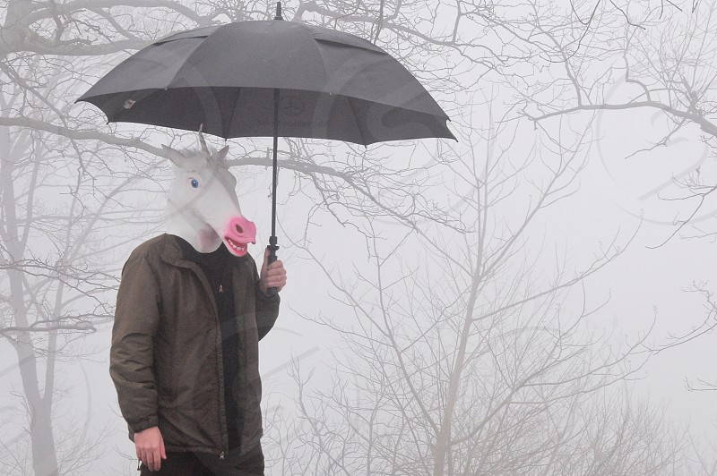 person in black shirt and brown jacket holding umbrella wearing white horse mask photo