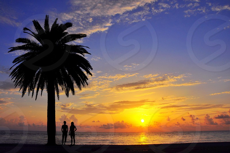man and woman under the sunset at the seashore photo