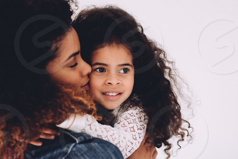 African american mother giving daughter a kiss on cheek photo
