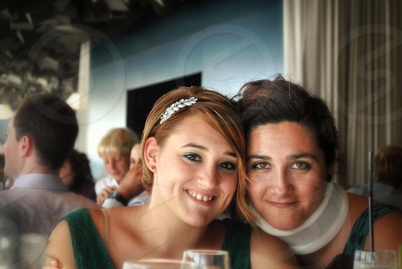 woman wearing green tank tops beside woman wearing neck-brace taking photo photo