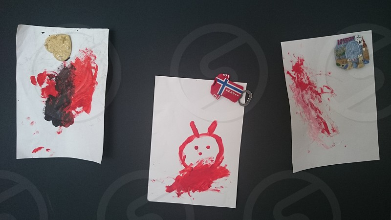 three red-white-and-black artworks on blackboard photo