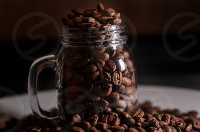 Small mason jar full of coffee beans. photo