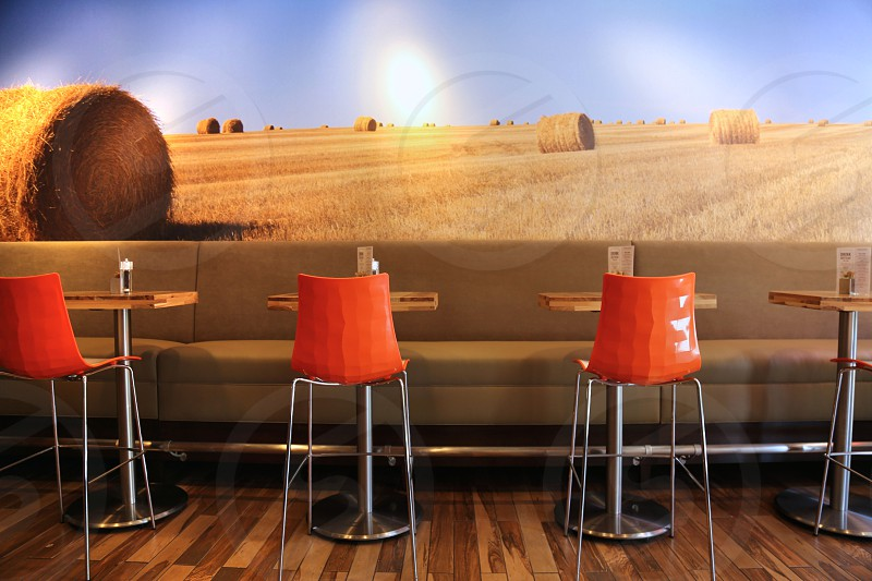 metal base stool chairs beside high tables and fabric padded sofa with hay bale and fields background photo