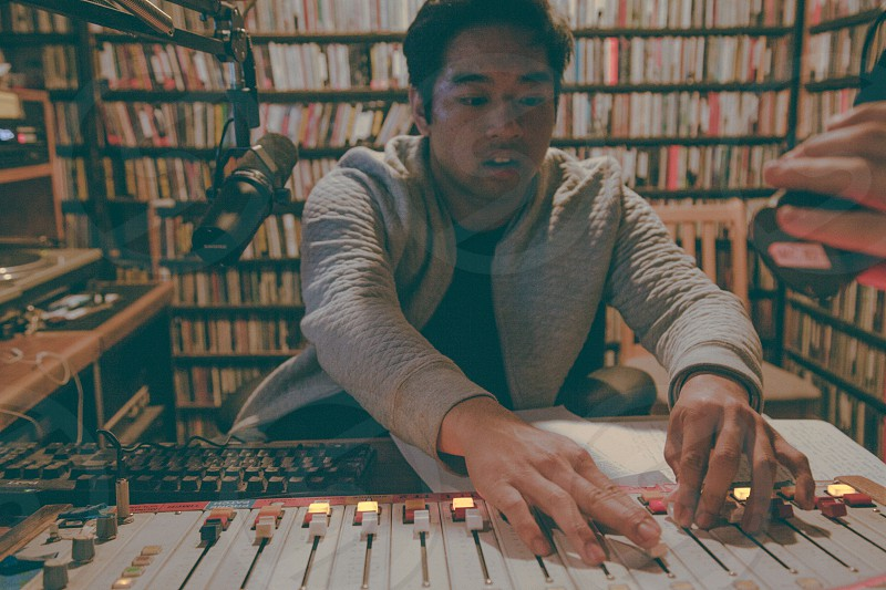 man in grey cardigan sitting behind a white audio mixer photo