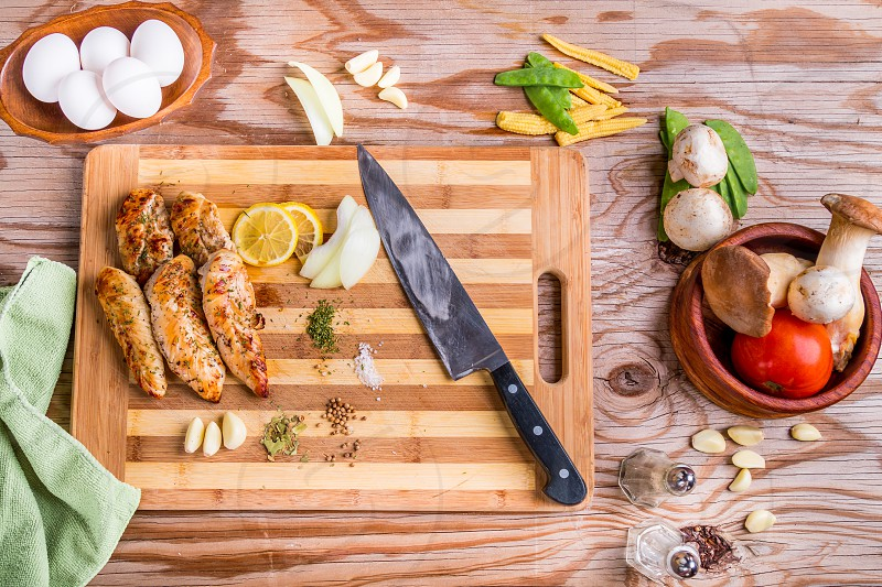Directly above over head top view of grilled chicken on a bamboo cutting board with eggs and vegetables photo