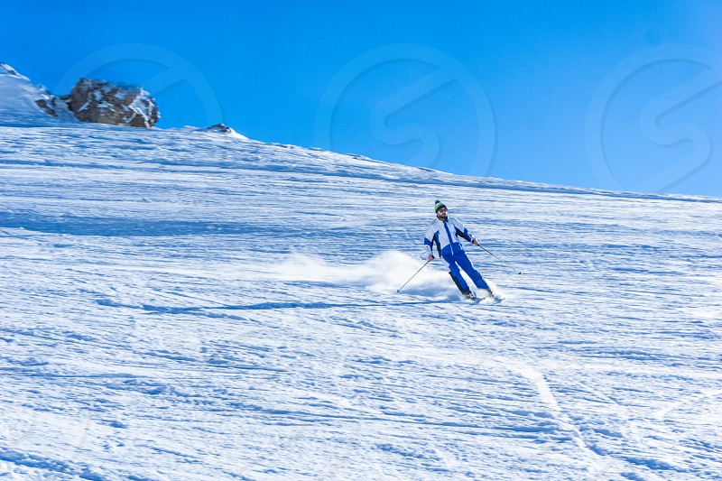 A young skier is skiing downhill in high mountains during a sunny day  photo