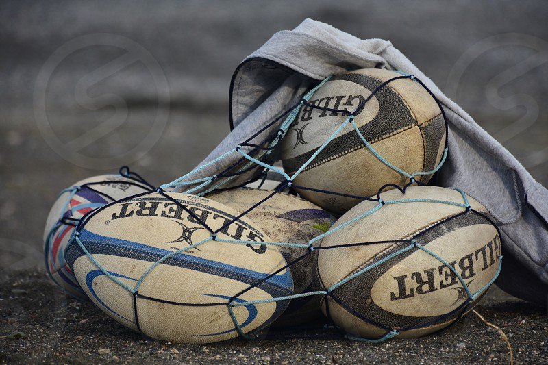 gilbert rugby balls in a net sack on the ground photo