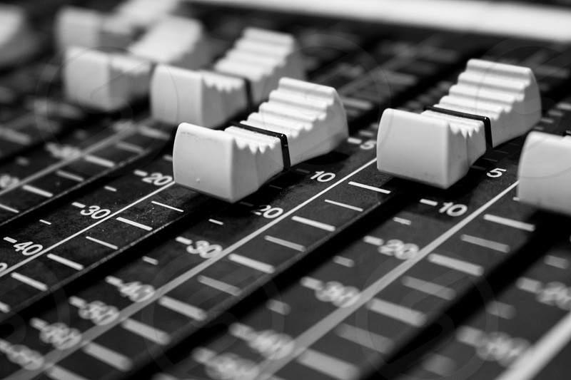 Closeup view of Faders on Professional digital Audio mixing control Console with zero decimal indicators photo
