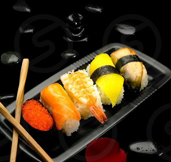 assorted sushi plate on black pebbles over black background photo
