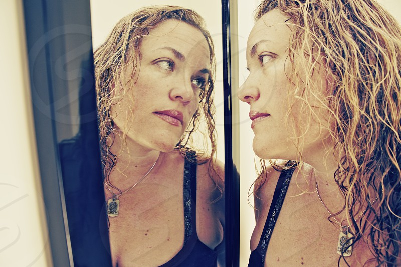a woman who is staring into her own reflection in self examination photo