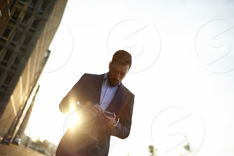 A young business man outside in an urban area of the city walking using his mobile phone in early morning sunrise photo