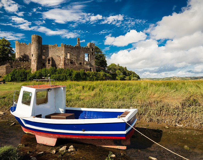 Laugharne Castle and a Fishing Boat. A small fishing boat moored on the river in front of Laugharne castle in Carmarthenshire Wales. photo