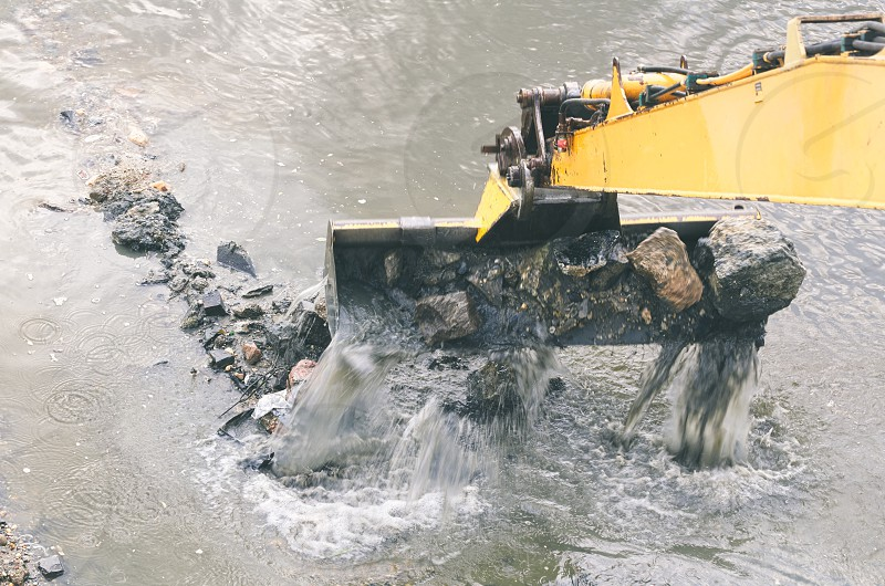 Yellow Excavator Cleans the River Bed Closeup photo