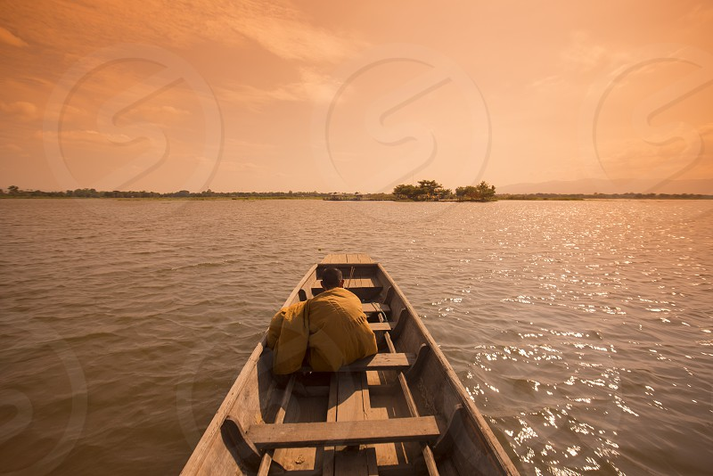 a woodboat on the way to  the Temple Island or wat Tiloke Aram Island at the lake of Kwan Phayao in the city of Phayao in North Thailand. photo
