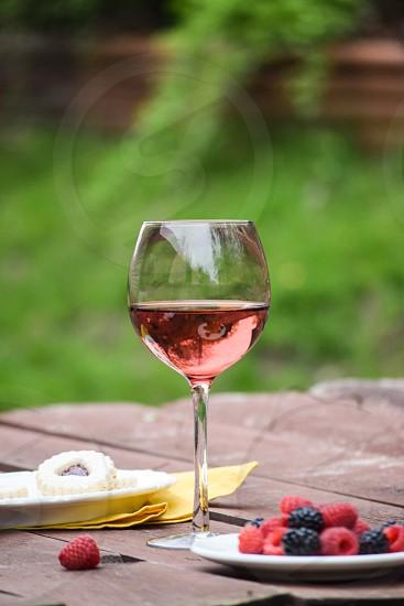 long stem wine glass near strawberries and raspberries on focus photography photo