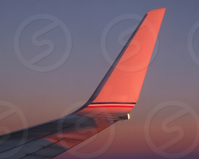 Tail of a plane reflects the pink sunset photo