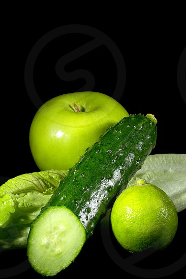 group of green vegetables and fruits over black background photo