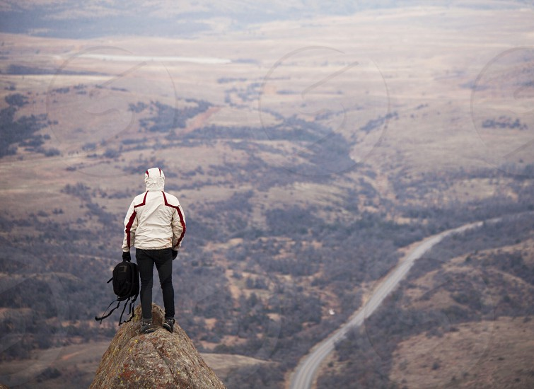 human standing on rock in mountains looking down photo