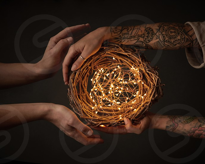 A wreath of branches with Christmas lights. The hands of a man and the hands of a woman with a tattoo are holding a wreath on a black background. photo