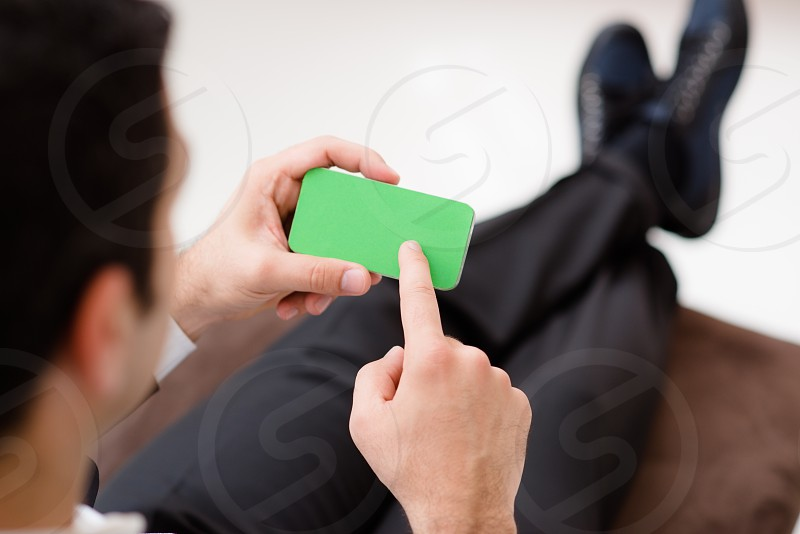 man; smartphone; phone; telephone; screen; internet; email; 40s; adult; browsing; business; businessman; caucasian; cell; cellular; comfortable; communication; corporate; couch; display; e-mail; finger; fingers; gesture; gesturing; green; hand; home; mail; male; mobile; monitor; multitouch; one person; people; person; relax; relaxed; sitting; smart phone; smart-phone; sofa; technology; touch; touching; touchscreen; web; wi-fi; wireless; working photo