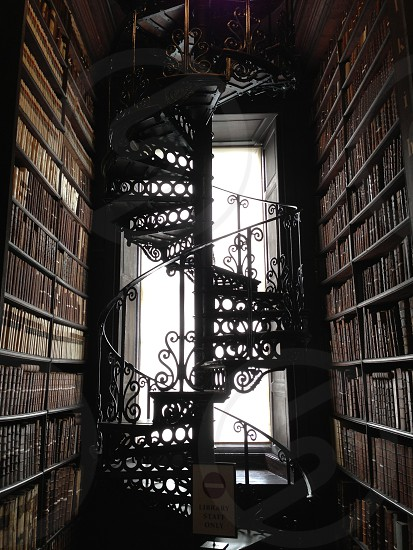 Winding iron staircase in the middle of a library. Silhouette.  photo