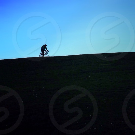 person riding bicycle on hill photo