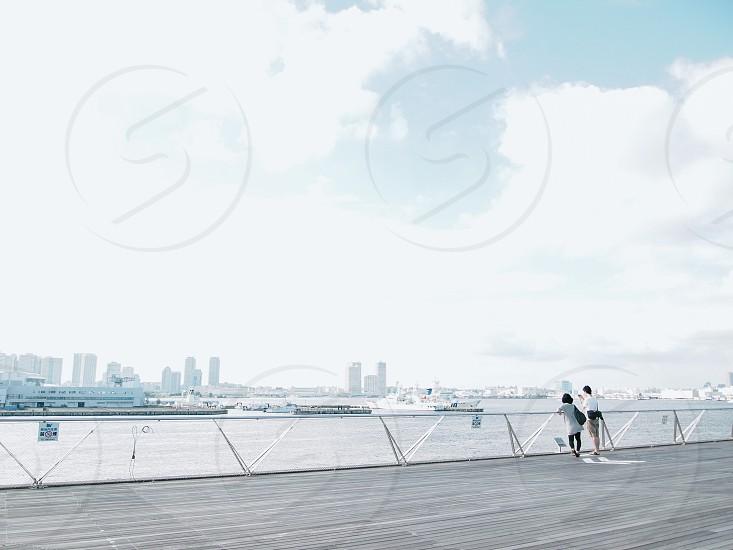 man and woman looking at sea view photo