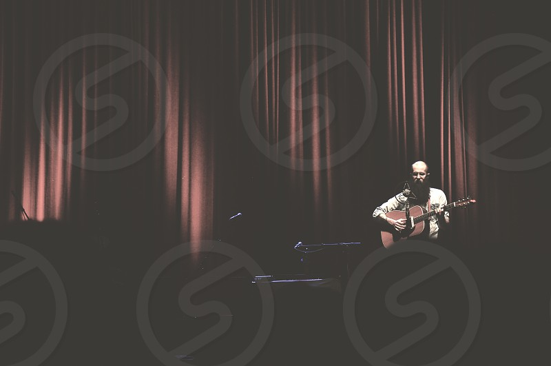 man playing guitar on stage photo