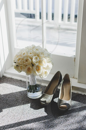 Bouquet and wedding shoe by the window photo